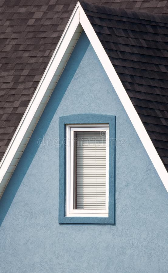 Grey roof, blue walls with window and white paintwork details. Minimalistic style stock image