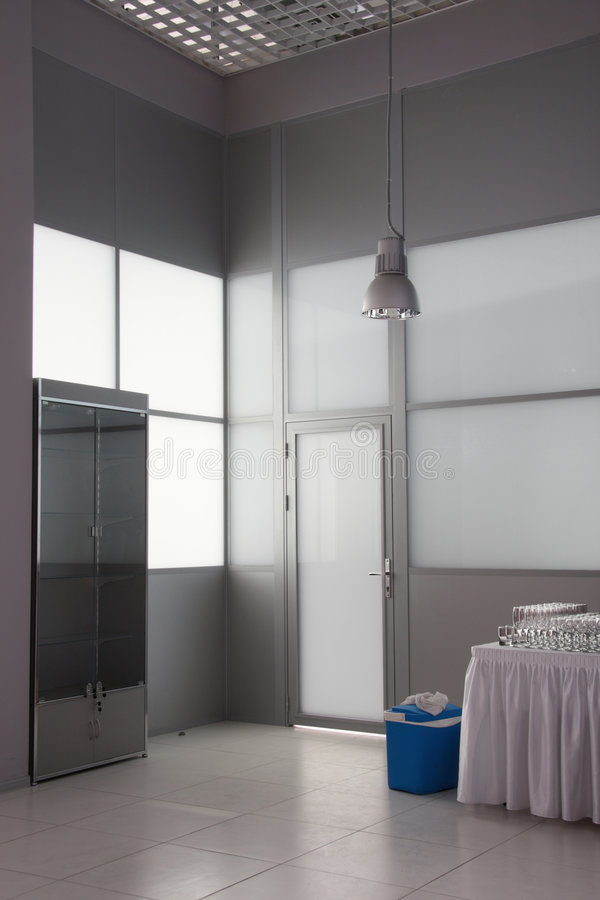 Grey room. Glass door, case and table with glasses in a subsidiary premise stock images