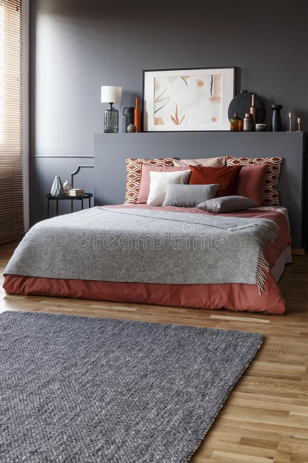 Grey rug in front of a king size bed with pillows and a painting stock images