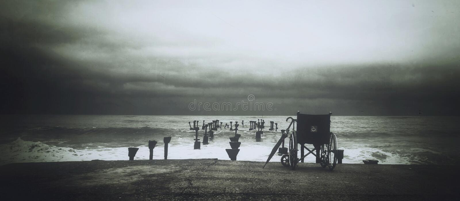 Grey Scale Photograph of Wheel Chair Near Water Sea royalty free stock image