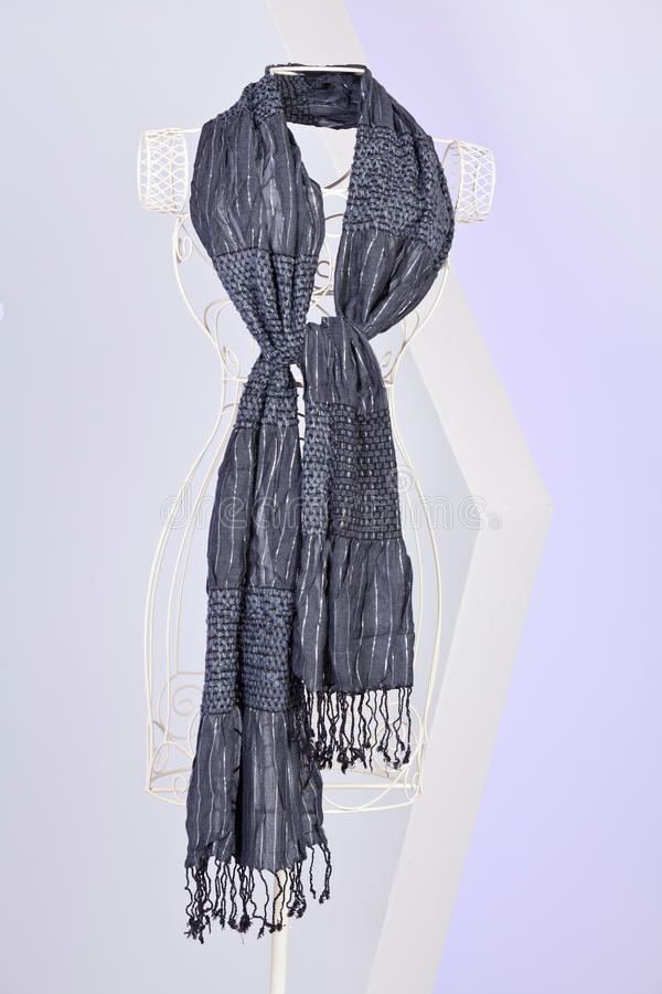 Grey scarf woven with fringes on mannequin. Gray knit scarf with fringe hanging on mannequin royalty free stock images