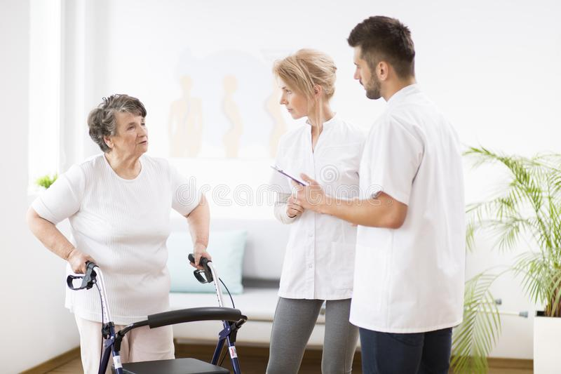 Grey senior lady with walker during physiotherapy with professional female doctor and male nurse royalty free stock photography