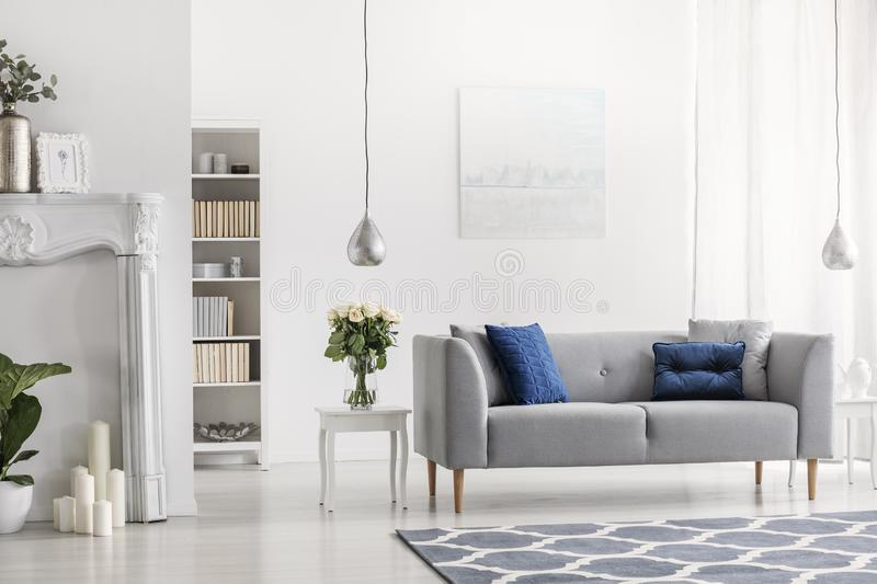 Grey settee with blue cushions in white elegant living room interior with flowers and painting. Real photo. Grey settee with blue cushions in white elegant royalty free stock photography
