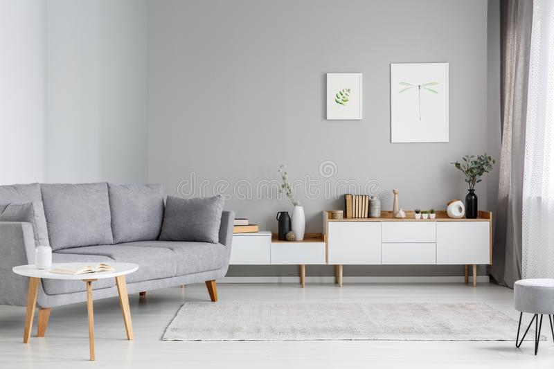 Grey settee near white cupboard in minimal living room interior. With posters on the wall. Real photo stock photo
