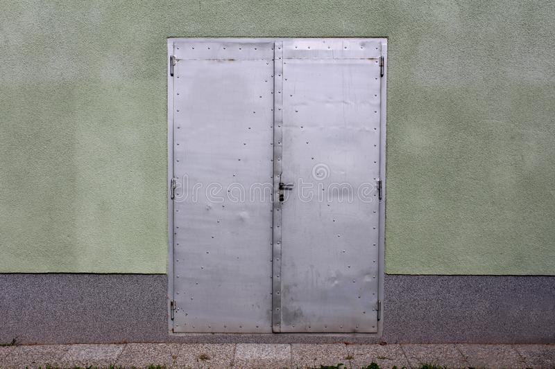 Grey sheet metal doors with small door handle mounted on house wall with stone tiles in front royalty free stock image