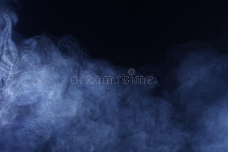 Grey Smoke azul no fundo preto fotografia de stock royalty free