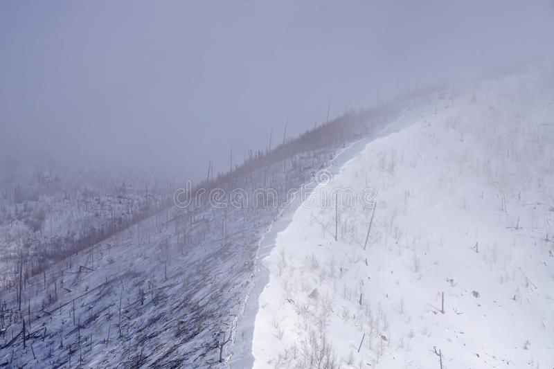 Snow-covered slope ridge in the fog. Grey snow weather, snow-covered slope ridge in the fog, mountain trip, no people stock photo