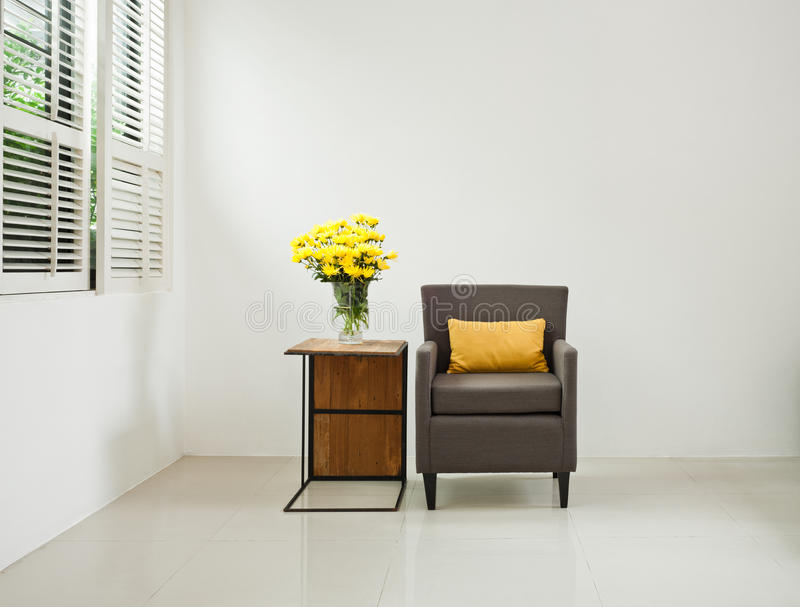 Grey sofa armchair in simple setting. Infront of lovered windows royalty free stock photography