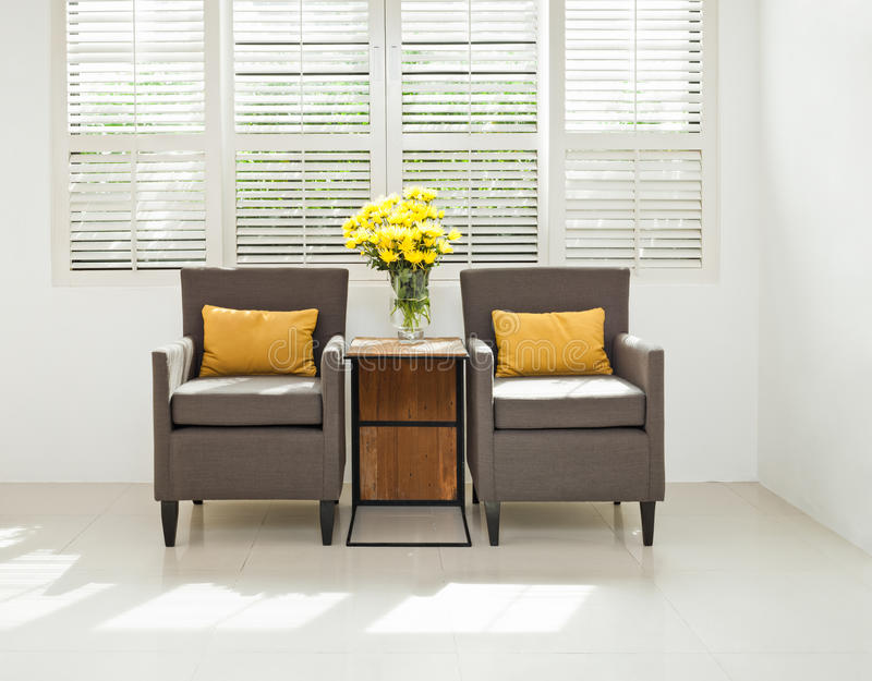 Grey sofa armchair in simple setting. Infront of lovered windows stock images