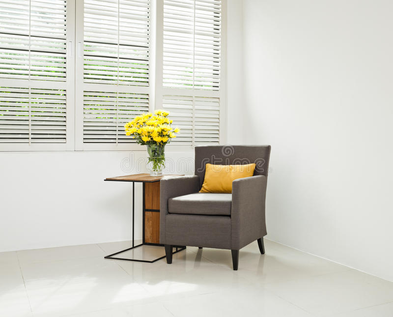 Grey sofa armchair in simple setting. Infront of lovered windows royalty free stock image
