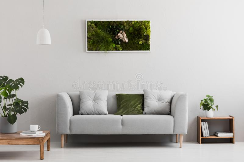 Grey sofa with pillow in real photo of bright sitting room interior with books on wooden shelf, coffee cup on table and garden in stock photography