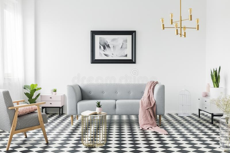 Grey sofa with pink blanket under poster in white flat interior with armchair and gold table. Real photo. Concept royalty free stock image