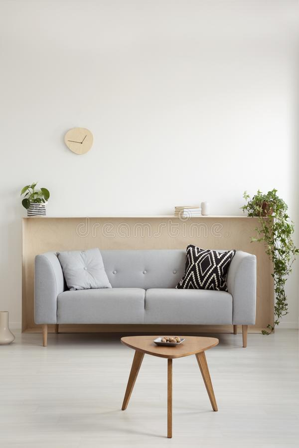 Grey sofa with two pillows in real photo of white living room in stock photo
