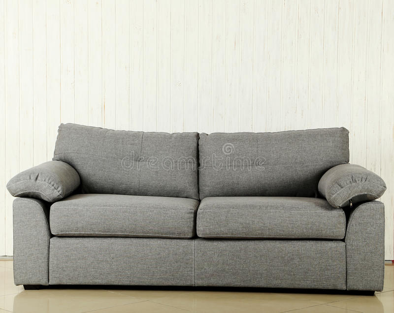 Grey sofa. On a white wood wall texture background royalty free stock photography