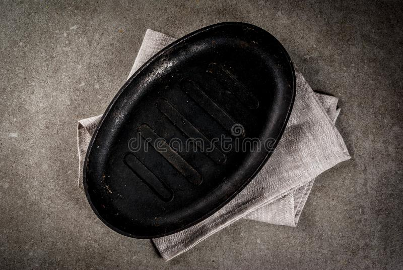 Culinary background with empty pan. Grey stone culinary background with empty black pan, top view copy space stock images