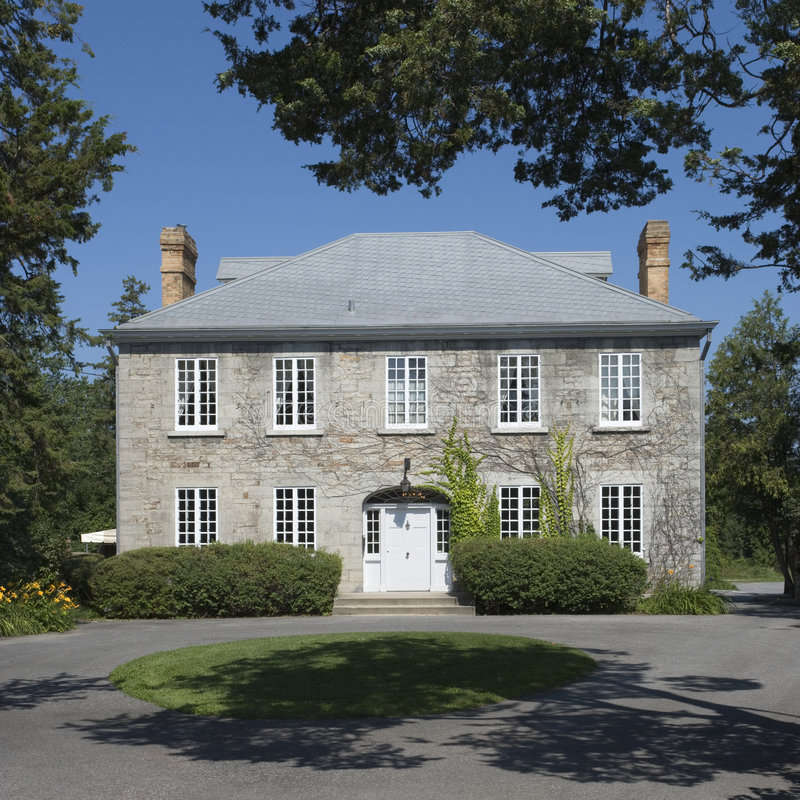 Grey stone Manor house. Front view of a well preserved Manor House royalty free stock photo