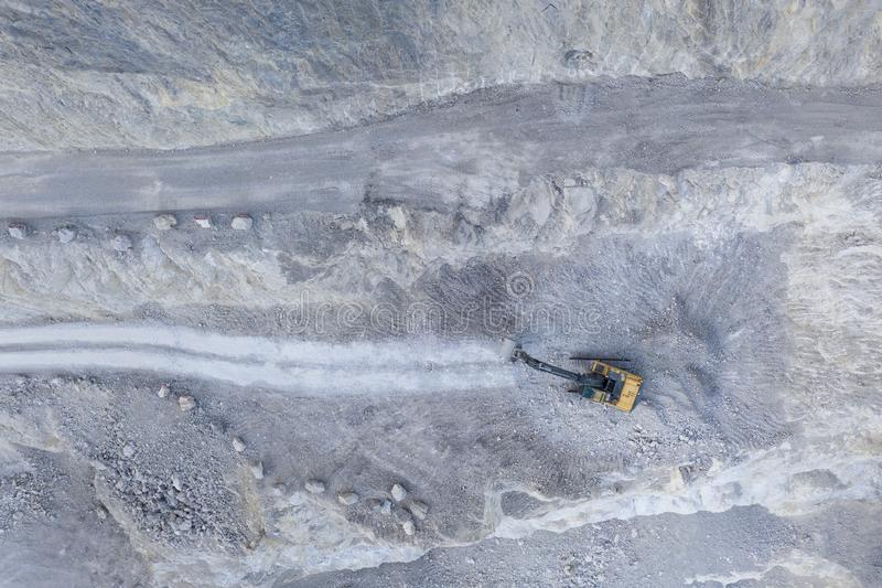 Grey stone quarry pit from aerial bird`s eye view. With heavy shovel excavator stock images