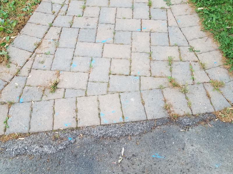 Grey stone tiles on path with blue marks and asphalt stock image