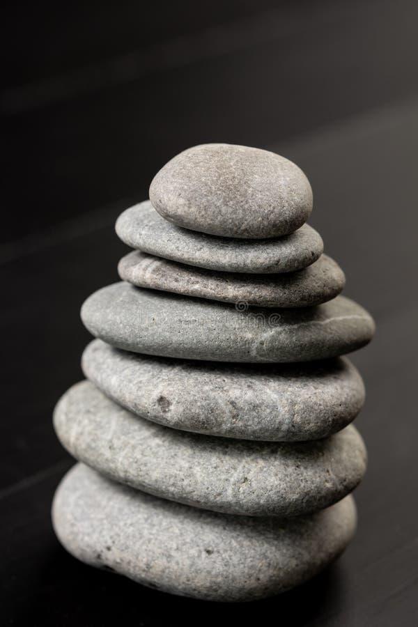 Grey Stones Balanced on the black background royalty free stock photo