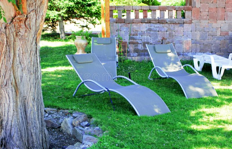 Grey sun loungers in garden stock images