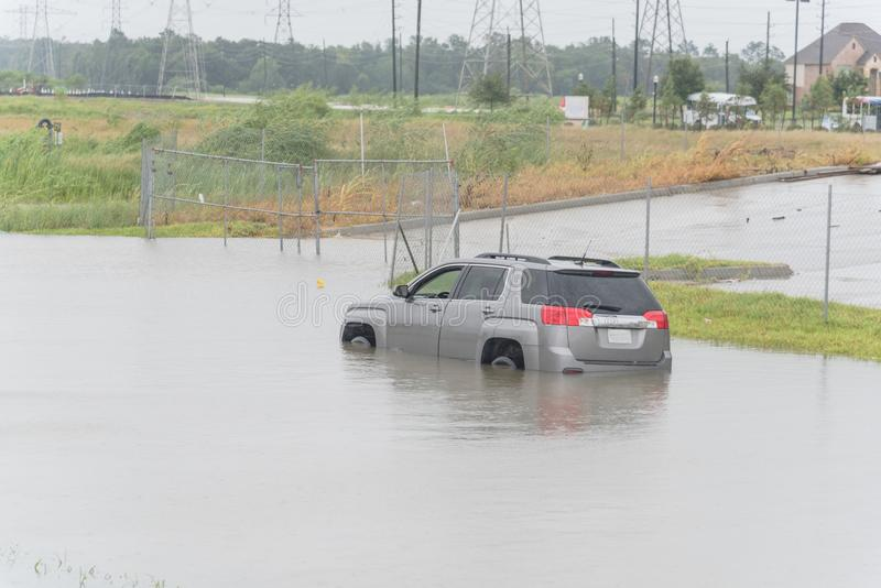 Car swamped by hurricane flood water in East Houston, Texas, USA. Grey SUV car swamped by flood water near construction zone row of power pylons. Submerged car royalty free stock images