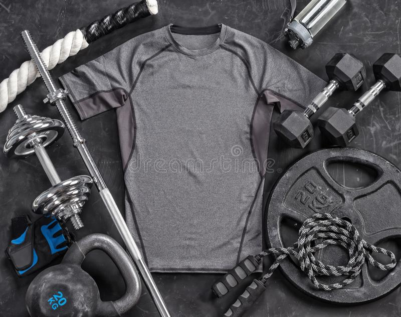 Grey t-shirt and sports equipment on a black background. Top view. Motivation. Copy space stock photos