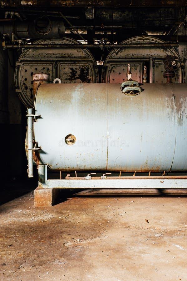 Grey Tank & forntida kokkärl för svart - övergett glasbruk arkivfoto