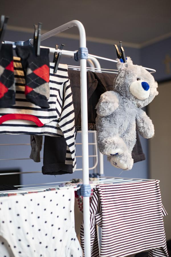 Grey teddy bear hanging dry on rack with clothes stock photo