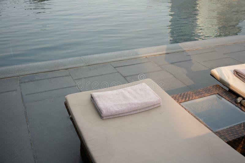 Grey Towel auf Entspannungspoolbett neben Swimmingpool lizenzfreie stockfotos