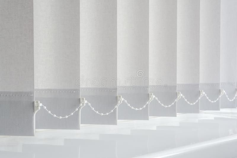 Grey vertical blinds hanging above white plastic window board royalty free stock image
