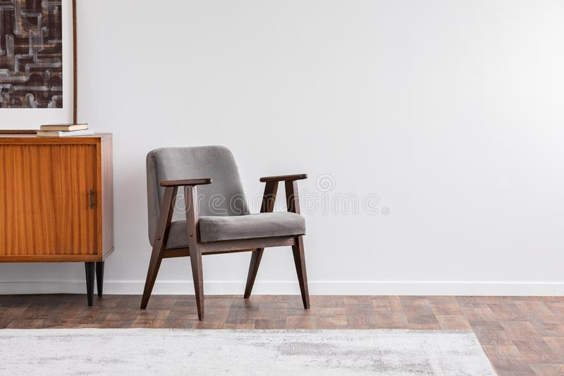 Grey vintage armchair next to retro cabinet with books, warm carpet on wooden fool, real photo stock photography