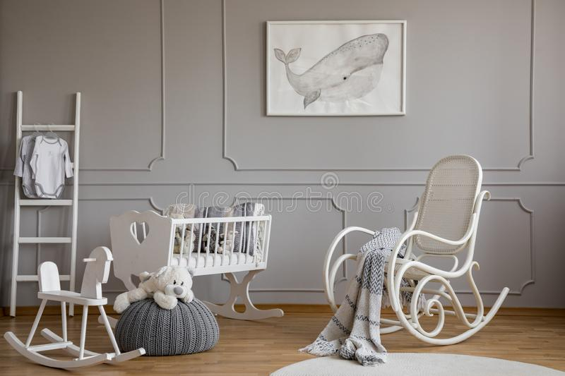 Grey whale on poster in classy baby room interior with white wooden rocking chair, rocking horse, crib and scandinavian ladder, royalty free stock photography