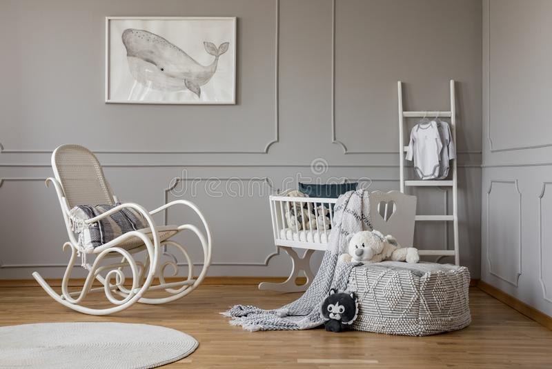 Grey whale on poster in stylish baby room interior with white wooden rocking chair and crib, copy space on empty wall. Grey whale on poster in stylish baby room stock images