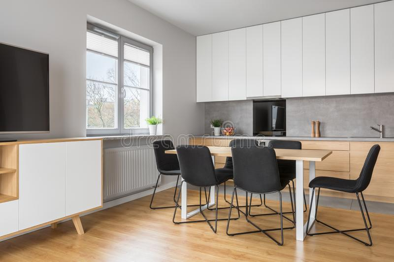 Grey and white apartment with wooden elements. Grey and white apartment with kitchen open to tv living room royalty free stock images