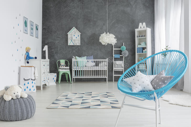Grey and white baby room. With round chair and cot stock photo