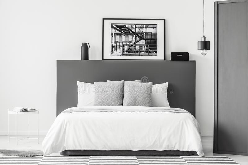 Grey and white bedroom interior. Patterned cushions on bed in grey and white bedroom interior with poster and lamp royalty free stock photo