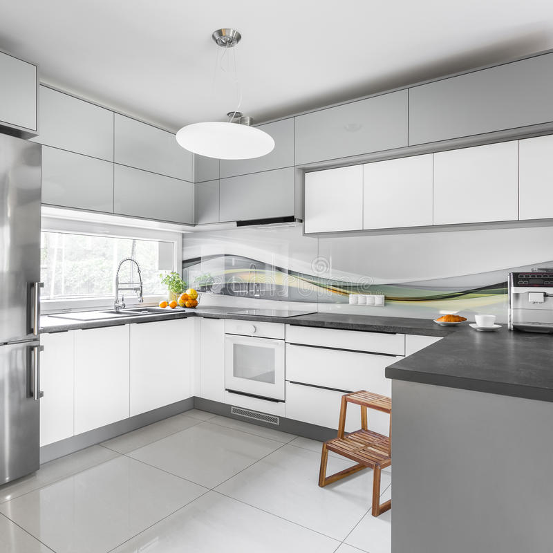 Grey and white kitchen. Modern design kitchen in grey and white with wooden step stool royalty free stock images