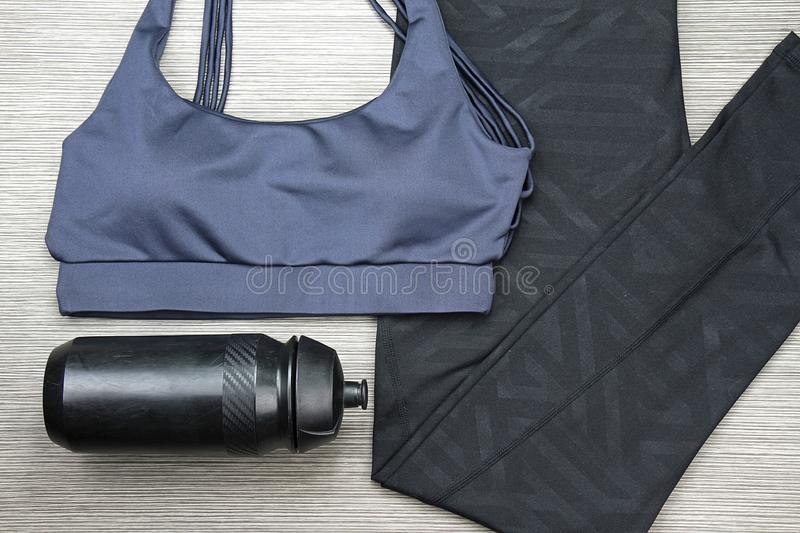 Grey women`s sports bra and Black Bicycle water bottle. Sport fashion and accessories. stock photography