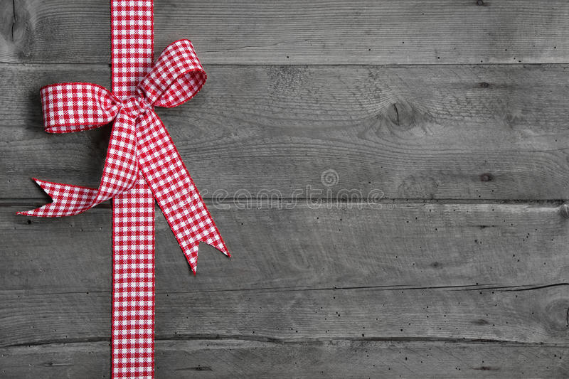Grey wooden background with red and white checkered bow as border royalty free stock photos