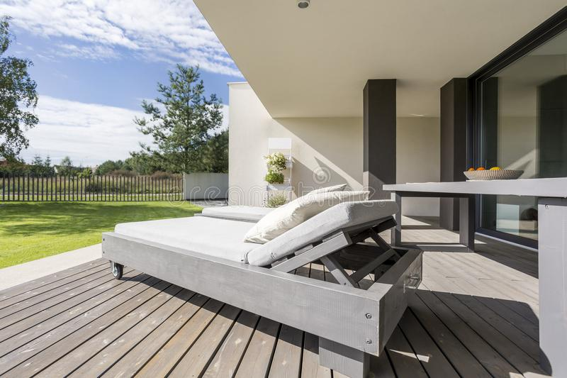 Grey wooden deckchair on patio. Grey wooden deckchair with pillows on patio of modern house with view on nature royalty free stock photography
