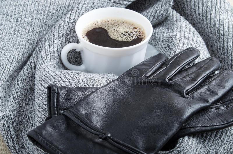 Grey wool scarf and leather gloves around the white cup of coffee. With blur and shallow depth of focus royalty free stock image