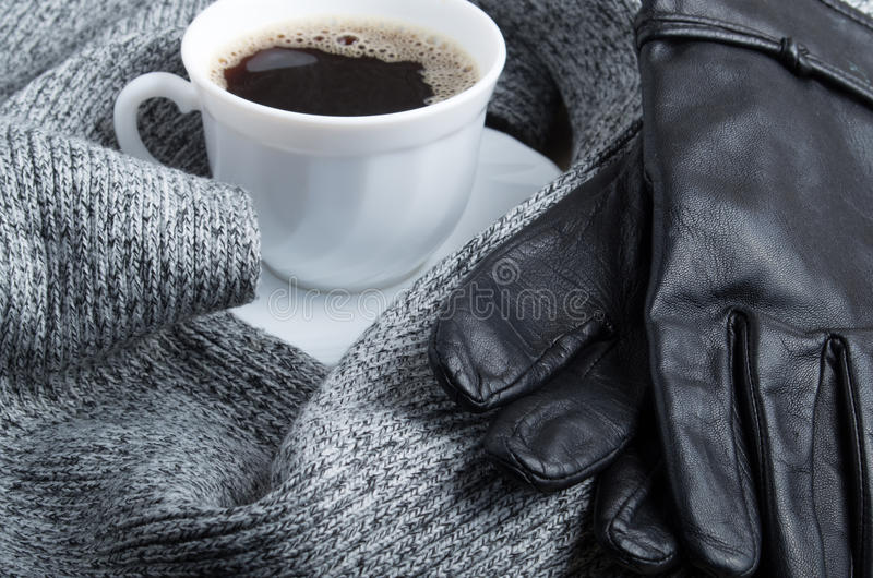 Grey wool scarf and leather gloves. Are surrounded by a hot cup of coffee with shallow depth of focus stock photography