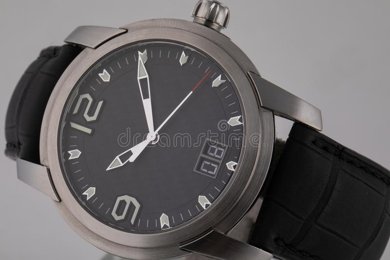 Grey wristwatch with black dial, silver clockwise, and chronograph on black leather strap isolated on white background. royalty free stock photos