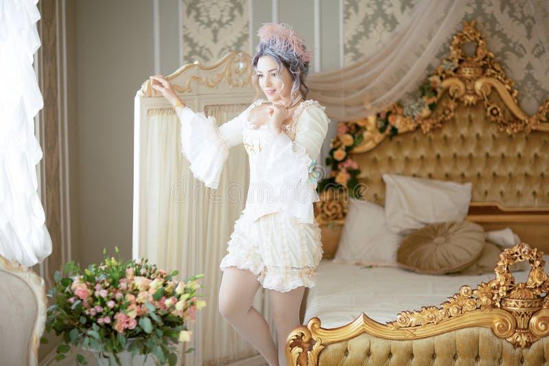 Greyhead kobieta w średniowiecznej gorsetowej historycznej sukni i bieliźnie pozuje w łóżku obrazy stock