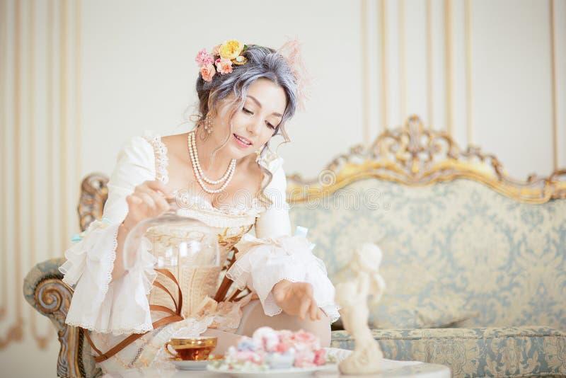 Greyhead kobieta w rokoko smokingowy pozować przed różowym tłem podczas gdy jedzący śniadanie obraz stock