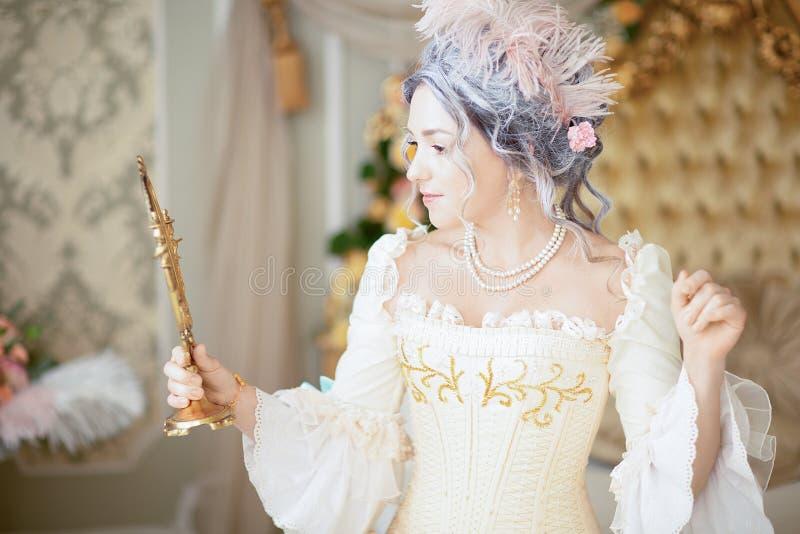 Greyhead kvinna i klänning och damunderkläder för medeltida korsett som historisk poserar i säng royaltyfria bilder
