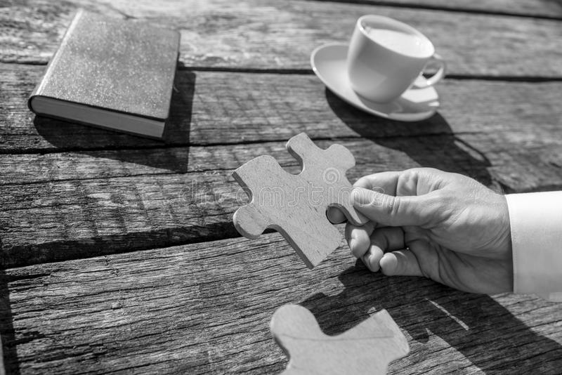 Greyscale close up on hand of unidentifiable business man holding puzzle piece stock images