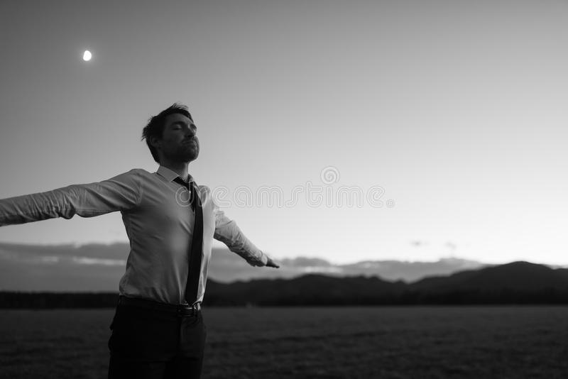 Greyscale image of businessman in white shirt and black tie stan royalty free stock photography