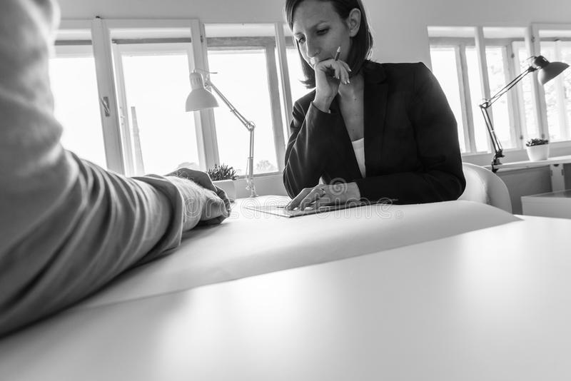 Greyscale image of businesswoman working on project over sheet o stock photos