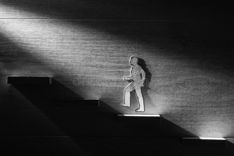 Greyscale image of cutouts of a man walking upwards royalty free stock image